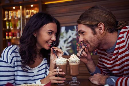 flirty: Flirty young couple drinking latte in cafe