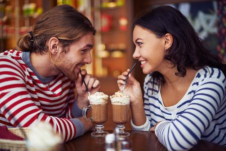 романтика: Счастливые молодые даты, имеющие латте во время отдыха в кафе Фото со стока