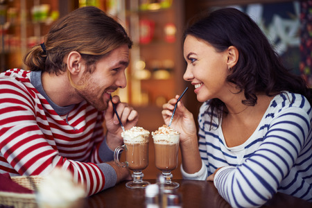 women coffee: Happy young dates having latte during rest in cafe Stock Photo