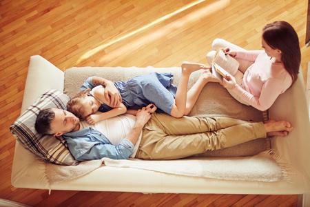 deitado: Família moderna de três relaxa no sofá