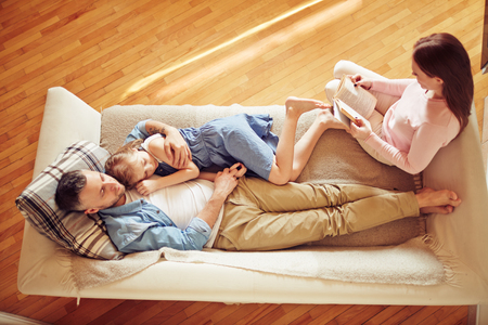 aile: Kanepe üzerinde rahatlatıcı üç modern aile Stok Fotoğraf