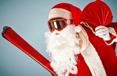 to ski: Santa Claus with red sack and ski equipment