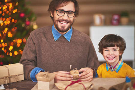 christmastide: Happy young man and his son preparing Christmas surprises for friends Stock Photo