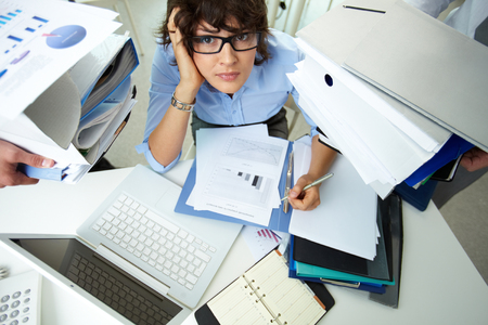 彼女の同僚が保有する文書の巨大な山に囲まれた気になる会計士 写真素材