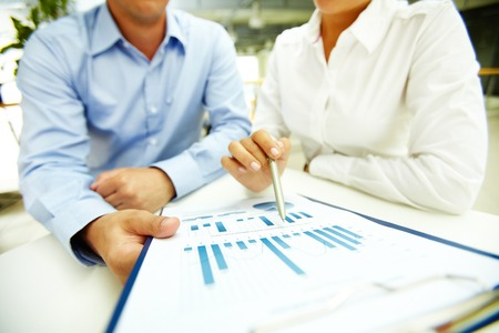 information point: Businesswoman with pen explaining data to colleague Stock Photo