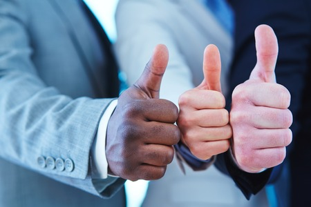 alright: Three business people showing thumb up gesture