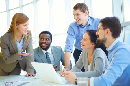 Pretty manager explaining her viewpoint upon project to co-workers Stock Photo
