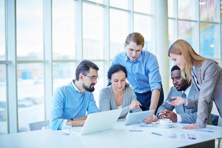Grupo de empleados de consultoría datos electrónicos al hacer el análisis