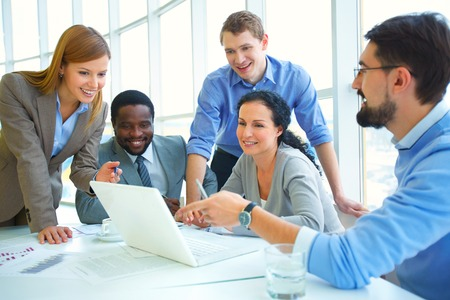 work group: Modern businesswoman making presentation and discussing it with colleagues