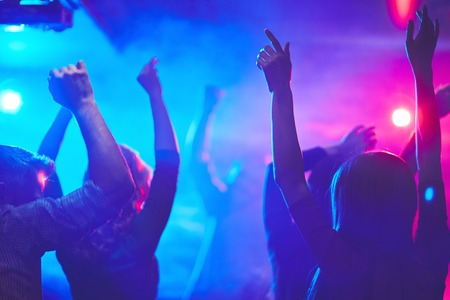 Group of dancing people with raised arms enjoying disco party Standard-Bild