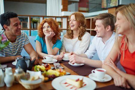 amigos hablando: Amigos felices que hablan mientras se relaja en el café Foto de archivo