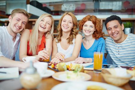 tomando jugo: Amigos alegres que se relajan en la cafetería entre los estudios