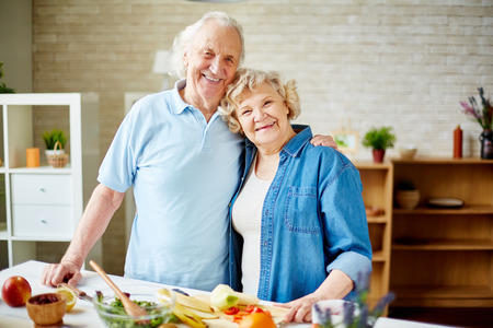 wife and husband: Cheerful seniors standing by table with fruits and looking at camera in the kitchen