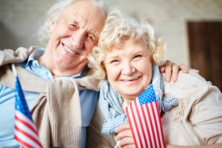 patriotic: Smiling seniors with flags of USA looking at camera Stock Photo