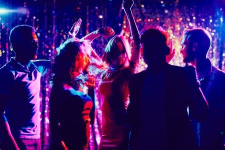 Grupo de los chicos y chicas bailando en el club nocturno