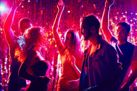 Friendly clubbers dancing at party Foto de archivo