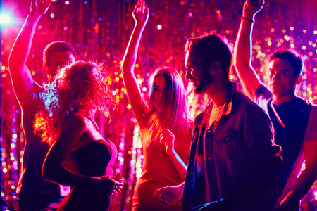 Friendly clubbers dancing at party Standard-Bild