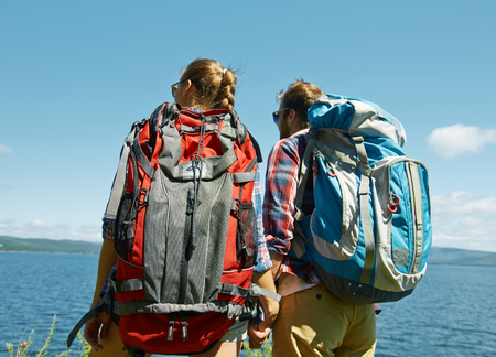 travel woman: Couple of young hikers with backpacks looking at sea