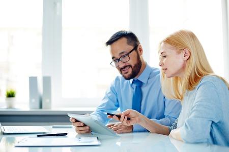 trabajadores: Dos trabajadores de oficina en discusiones datos de panel táctil en la reunión