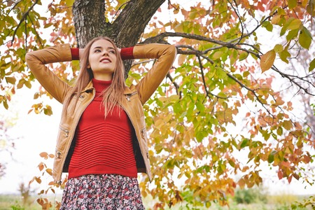 restful: Restful girl in leather jacket and red pullover standing by tree trunk in park