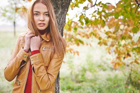 chaqueta: Mujer bonita joven en la chaqueta de cuero que mira la cámara mientras está de pie por el tronco de un árbol en el parque