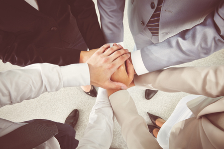 Hands of business partners making pile photo