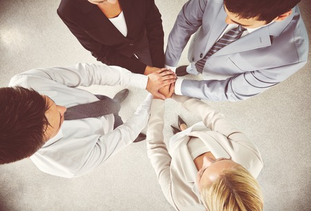 altogether: Business team keeping their hands in pile Stock Photo