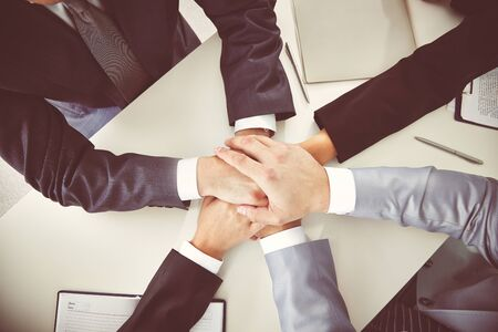 altogether: Hands of business partners on desk Stock Photo