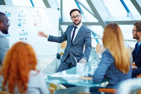 gerente: Hombre de negocios asiático que presenta la revisión de los datos financieros a los colegas