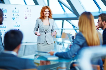 executive women: Pretty manager explaining her point of view to colleagues at meeting Stock Photo