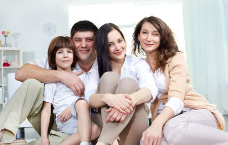 Affectionate family of four looking at camera at home photo