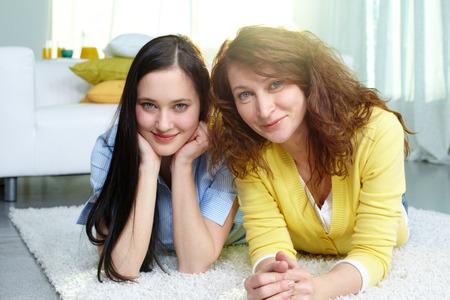 mama e hija: Madre reparador y su hija tendida en el suelo en casa