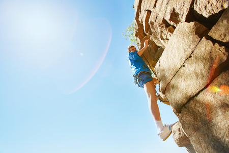activewear: Young sportsman in activewear climbing the rock