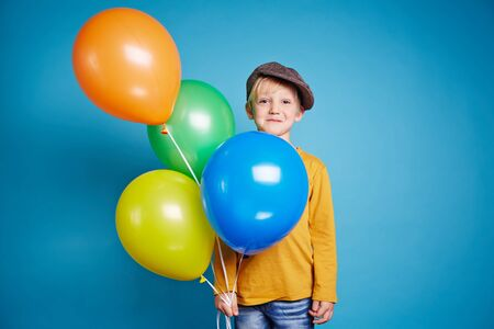 balloons: Little boy with balloons looking at camera Stock Photo