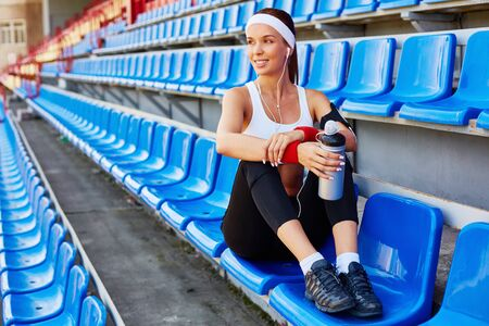 activewear: Happy fit woman with container of water having break after workout Stock Photo