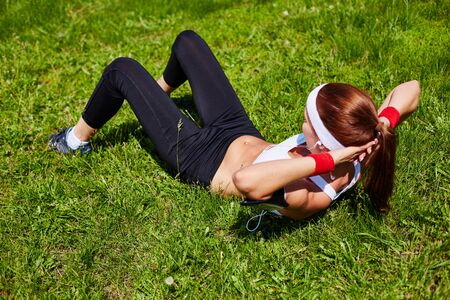 girl lying: Fit girl lying on grass and doing situps
