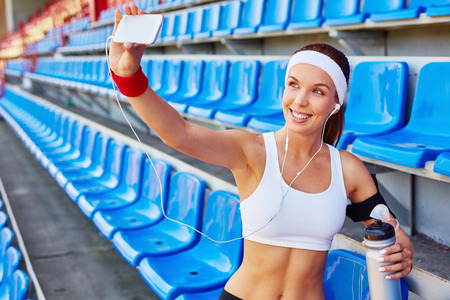 activewear: Active girl making her selfie at stadium
