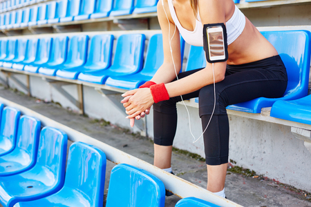 activewear: Fit girl in activewear sitting at stadium and listening to music