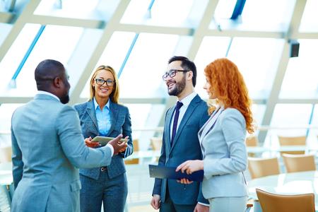 reuniones empresariales: Colegas multiétnicas felices que hablan en oficina