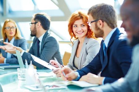 gente exitosa: Empleado bastante joven mirando a su colega durante la discusión de los datos