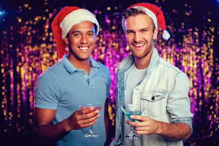 clubber: Two happy Santa guys with cocktails looking at camera at party Stock Photo