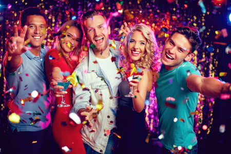 Group of ecstatic friends with cocktails looking at camera at party