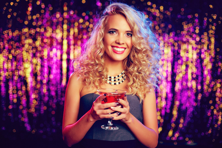 beautiful blonde: Smiling girl with cocktail looking at camera at party Stock Photo