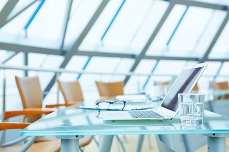 ノート パソコンと空の会議ホールで職場の水のグラス