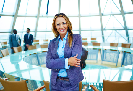 businesswoman suit: Pretty young businesswoman in suit looking at camera in conference hall