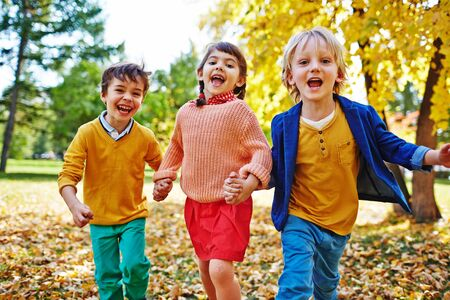 ecstatic: Ecstatic children looking at camera in park Stock Photo