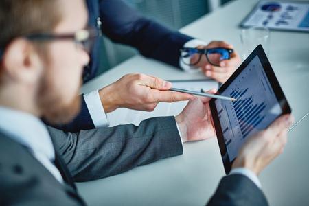 Zakenman die touchpad met gegevens die worden verklaard door zijn collega Stockfoto