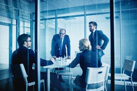 ejecutivo en oficina: Grupo de trabajadores de oficina escuchando a su colega en la reuni�n Foto de archivo