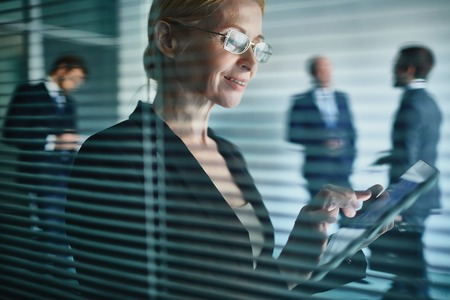 executive woman: Mature employee using touchpad at work Stock Photo
