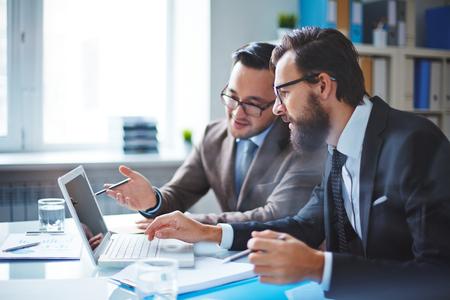 hombre de negocios: Dos empleados en discusiones sobre datos electrónicos en la reunión